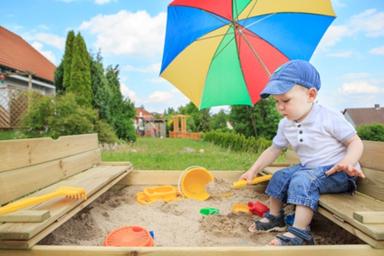 Kind im Holz Sandkasten